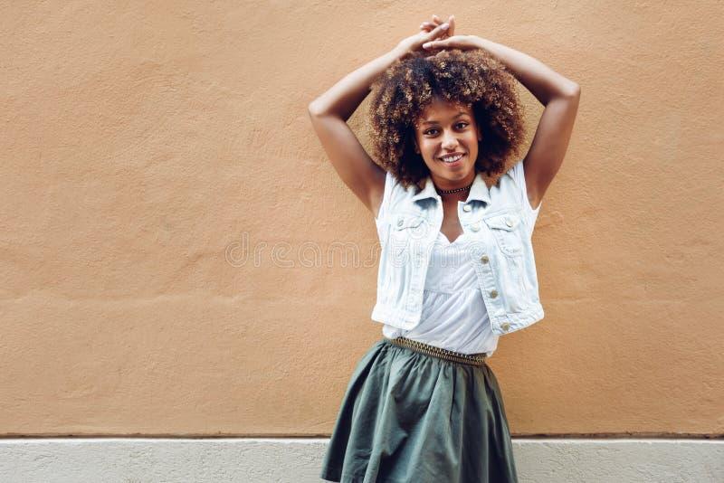 Ung svart kvinna, afro frisyr som ler i stads- bakgrund arkivbild