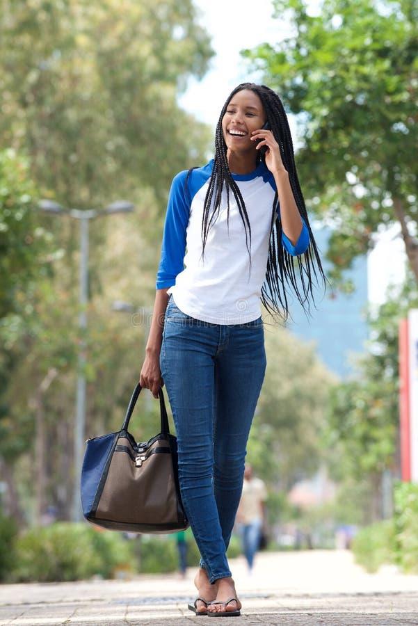 Ung svart kvinna för full längd som går i staden och talar på mobiltelefonen arkivfoto