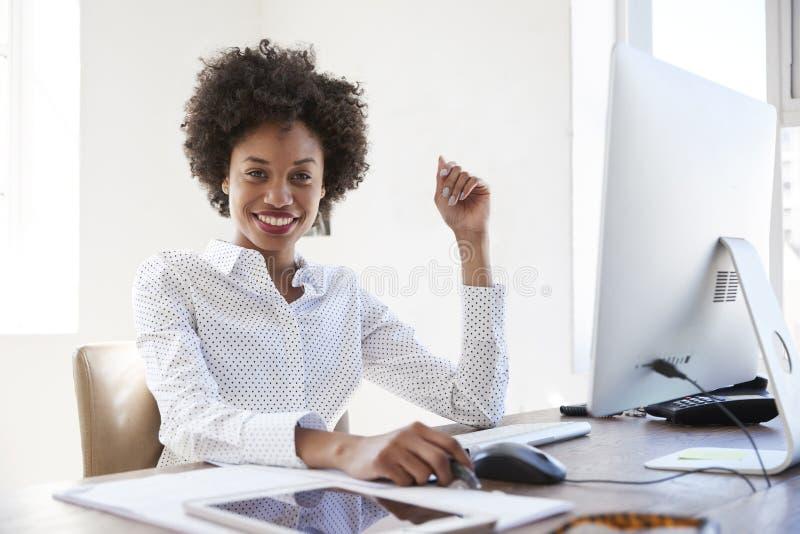 Ung svart kvinna i ett kontor som ler till kameran, slut upp fotografering för bildbyråer