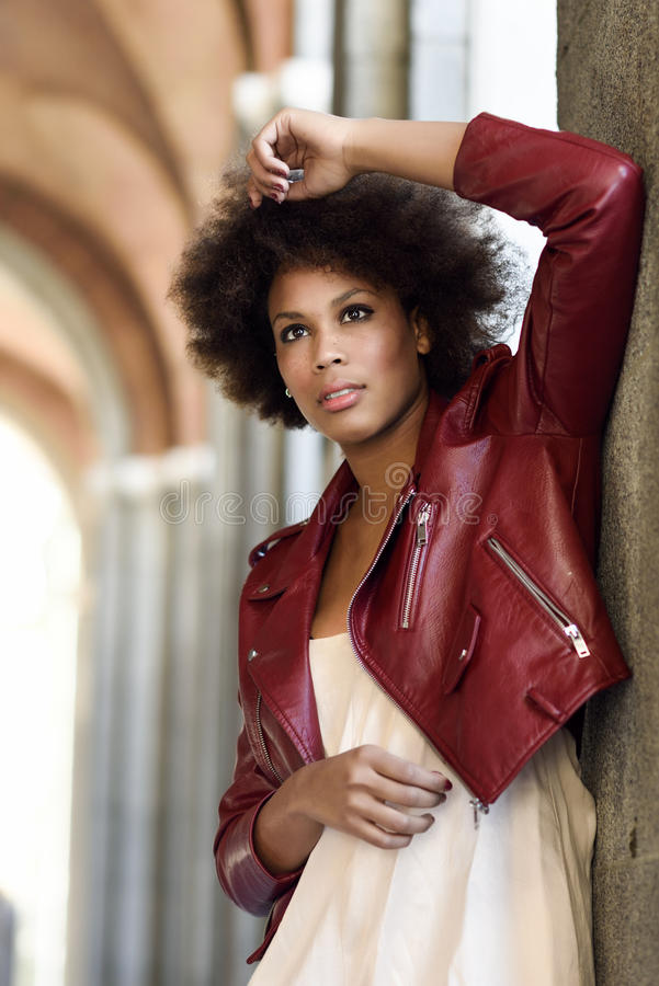 Ung svart kvinna med afro frisyranseende i stads- backgrou royaltyfria foton