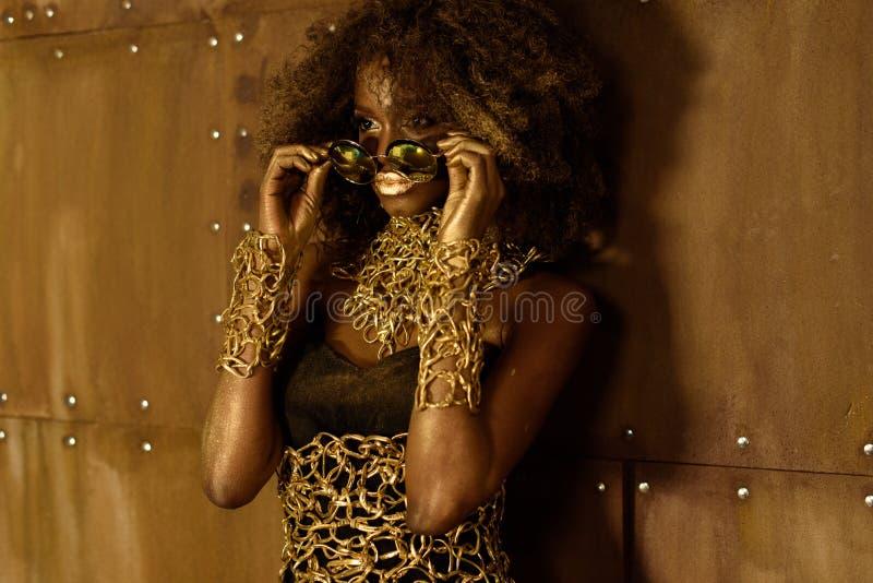 Ung svart kvinna med afro hår som bär guld- tillbehör och makeup som sätter på solglasögon som bort ser arkivfoton