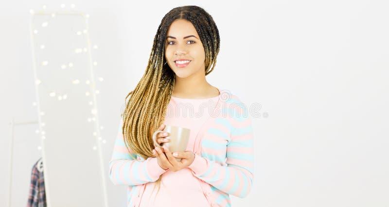 Ung svart kvinna med afro le f?r frisyr Flicka med den varma drinken för kopp som bär den rosa klänningen h?rlig f?r studiokvinna royaltyfri fotografi