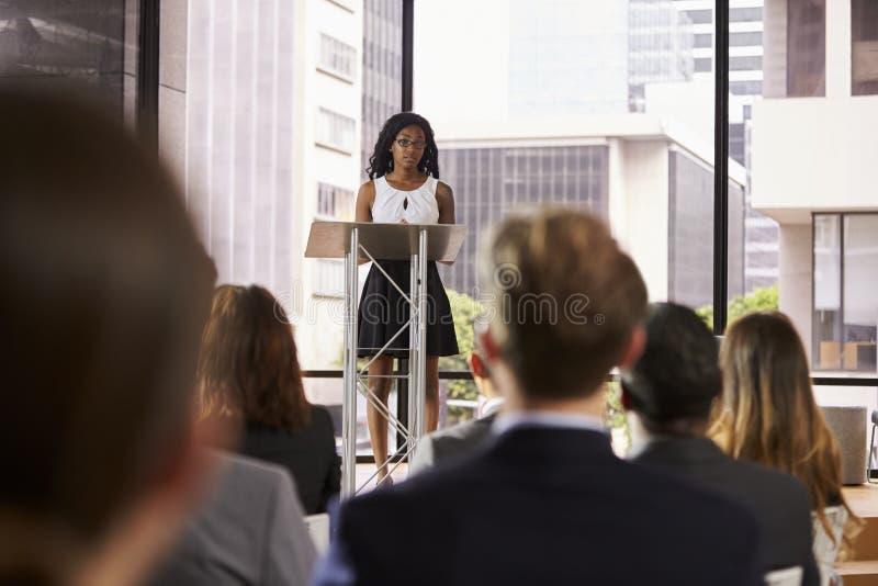 Ung svart kvinna på korpulpet som framlägger seminarium till åhörare arkivfoton