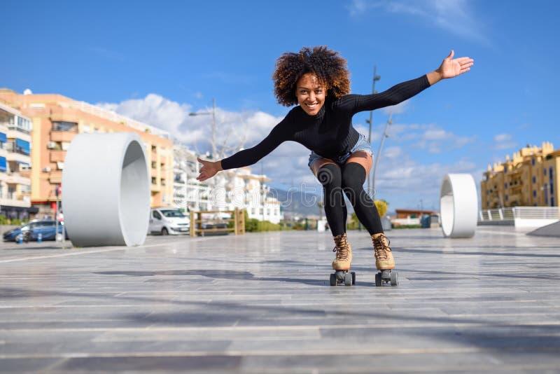 Ung svart kvinna på rullskridskor som utomhus rider på den stads- gatan med öppna armar Le flickan med den afro frisyren royaltyfria bilder