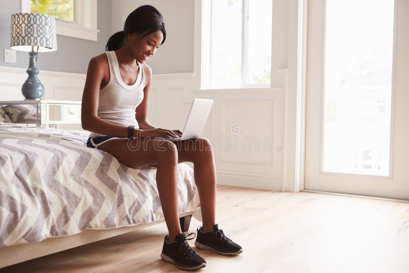Ung svart kvinna som är klar för övning, genom att använda bärbar datordatoren arkivfoto