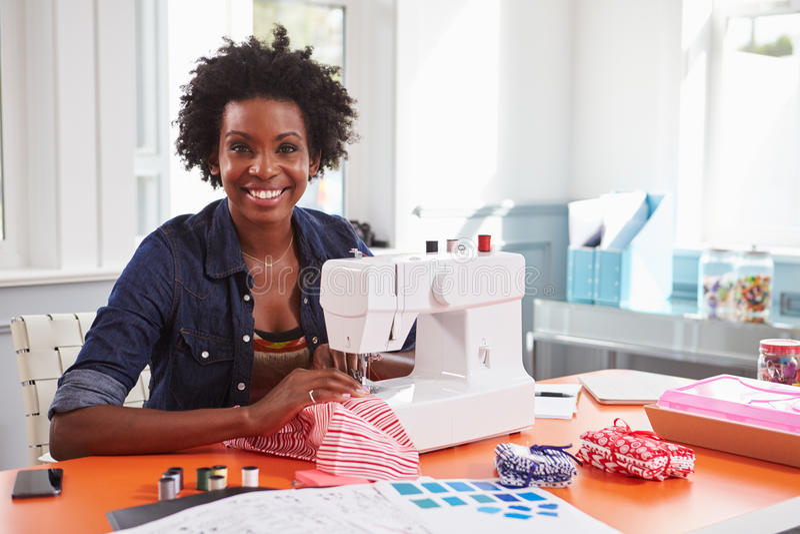 Ung svart kvinna som använder en symaskin som ser till kameran royaltyfri bild