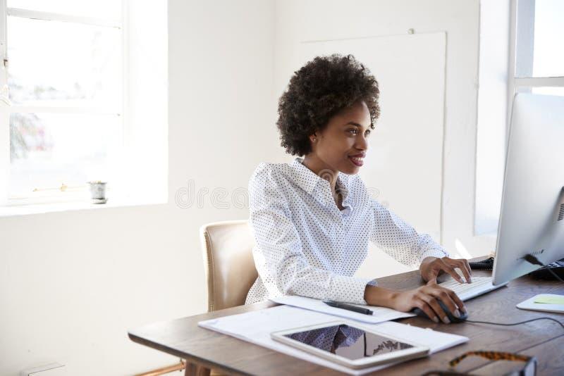 Ung svart kvinna som arbetar på datoren i ett kontor, slut upp royaltyfria bilder