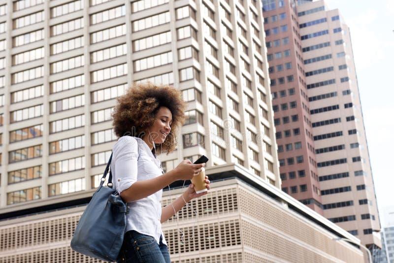 Ung svart kvinna som går och lyssnar till musik på stadsgatan royaltyfria bilder