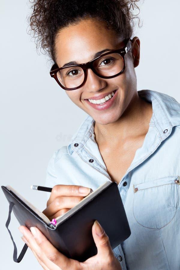 Ung svart kvinna som hemma tar anmärkningar royaltyfri fotografi