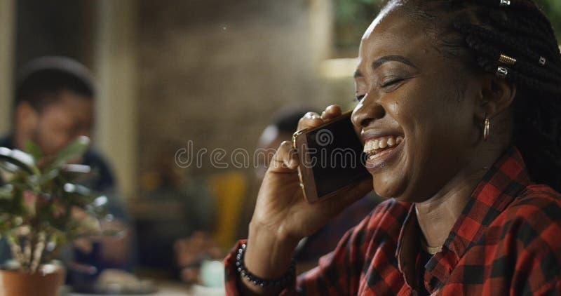 Ung svart kvinna som pratar på hennes mobiltelefon arkivfoto