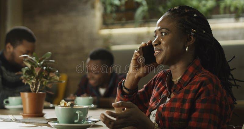 Ung svart kvinna som talar på hennes mobiltelefon royaltyfri bild