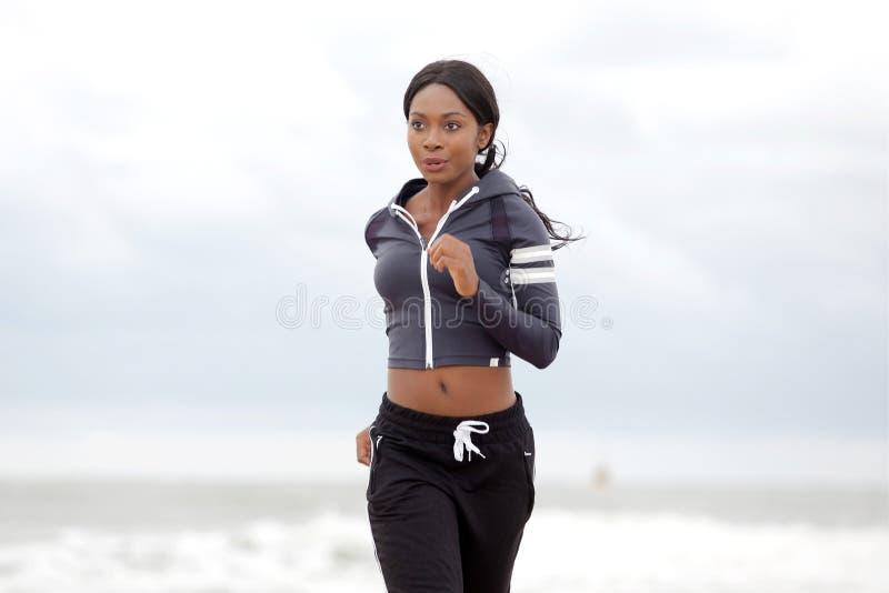 Ung svart kvinna som utomhus joggar royaltyfri bild