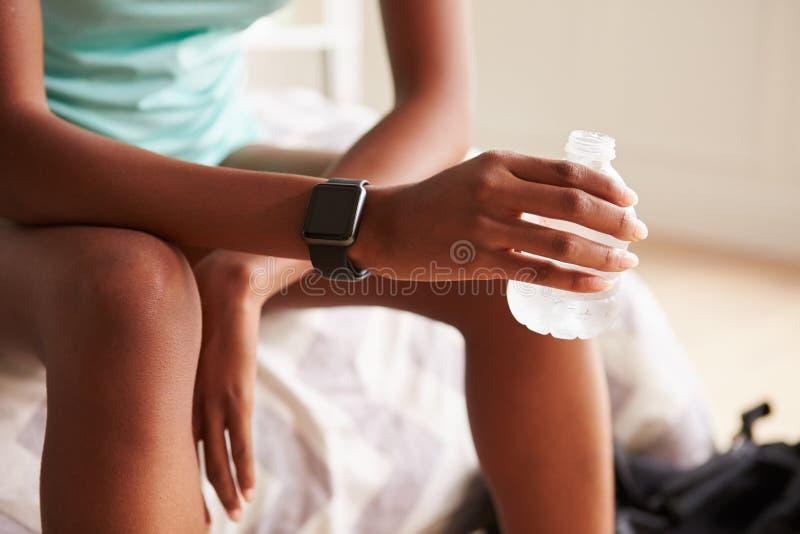 Ung svart kvinnainnehavflaska av vatten, närbilddetalj royaltyfria bilder