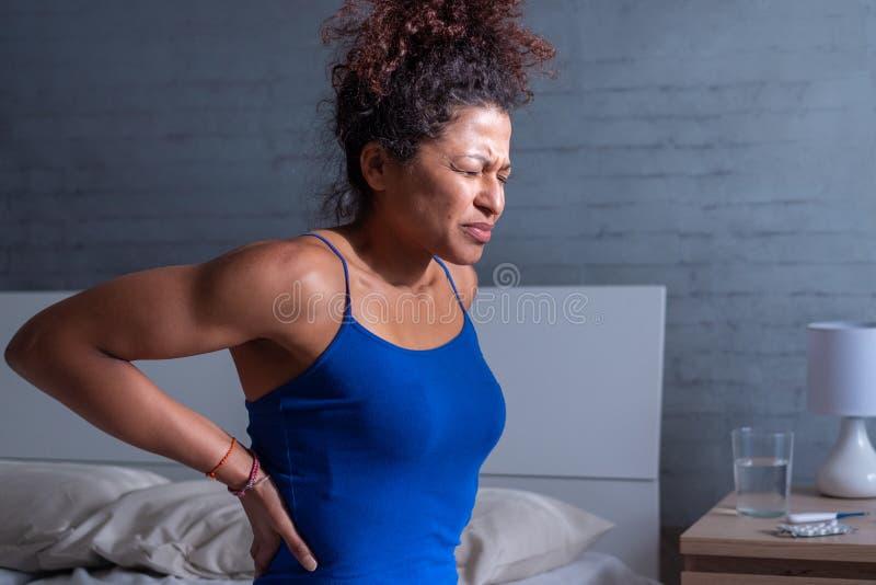 Ung svart kvinnakänsla tillbaka smärtar i morgonen arkivfoto