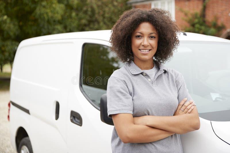 Ung svart kvinnlig tradesperson som står bredvid hennes vita skåpbil med armar, korsade, slutet upp arkivbilder