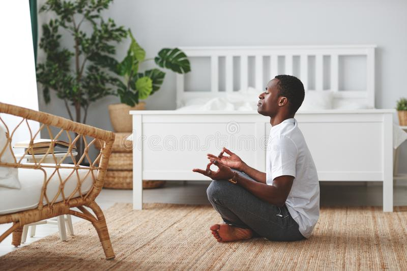 Ung svart man som gör yoga och hemma sitter i lotusblommaposition fotografering för bildbyråer