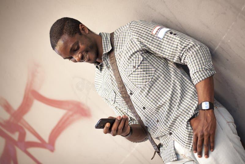 Ung svart man som kontrollerar meddelanden på hans smarta telefon royaltyfri foto