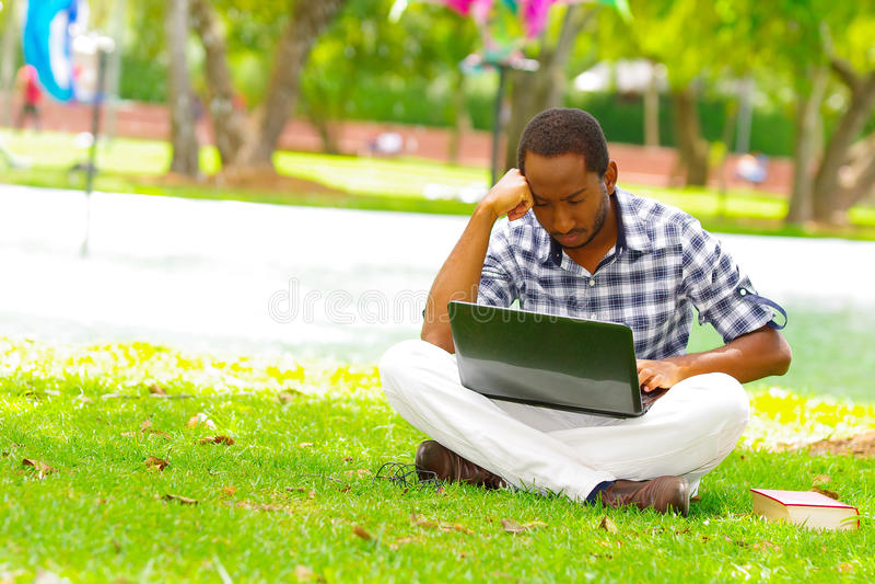 Ung svart man som ner sitter på grönt gräs och arbete i hans dator i staden av Quito Ecuador royaltyfri foto