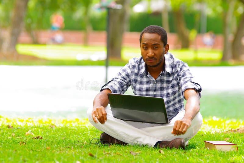 Ung svart man som ner sitter på grönt gräs och arbete i hans dator i staden av Quito Ecuador royaltyfri bild