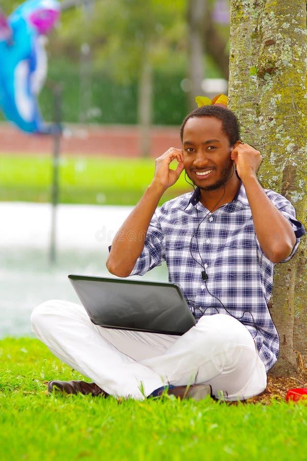 Ung svart man som ner sitter på grönt gräs och arbete i hans dator, och lyssnande musik med hans posera för hörlurar royaltyfria foton