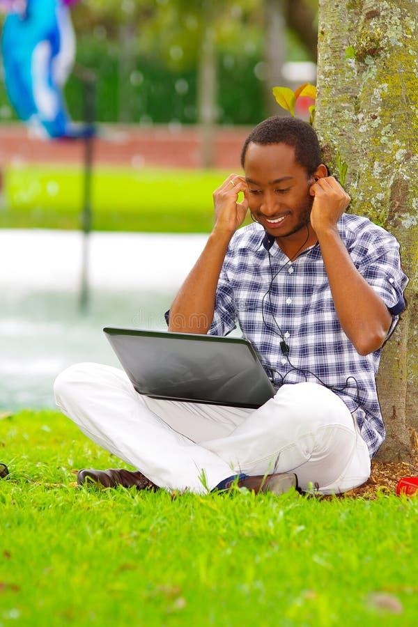 Ung svart man som ner sitter på grönt gräs och arbete i hans dator, och lyssnande musik med hans posera för hörlurar royaltyfri bild