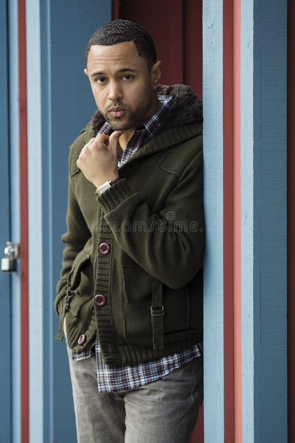 Ung svart man som plattforer i blå dörröppning royaltyfri bild
