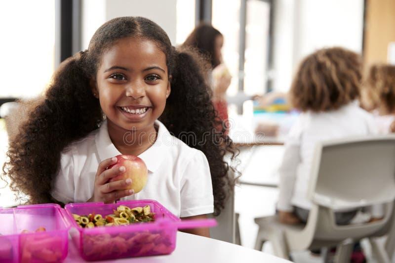 Ung svart skolflicka som sitter på en tabell som ler och rymmer ett äpple i ett dagisklassrum under hennes lunchavbrott, nära u fotografering för bildbyråer