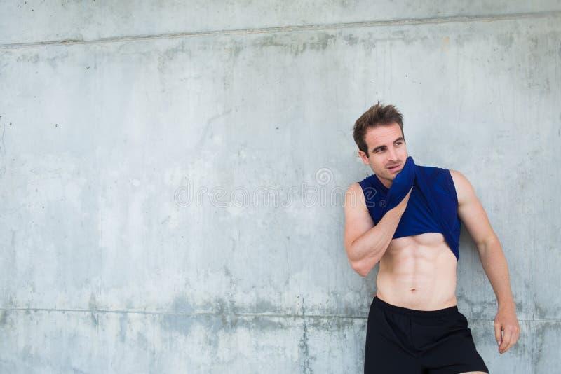 Ung svettas manlig jogger som tar avbrottet, når utbildning royaltyfri bild