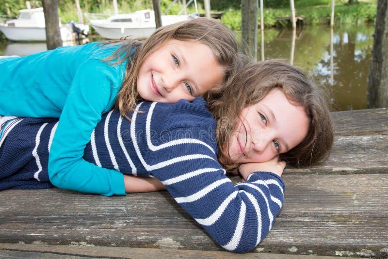 Ung syster som kramar flickan för litet barn, closeupstående av den lyckliga familjen, gulliga barnflickor som är utomhus- i vårt arkivbilder
