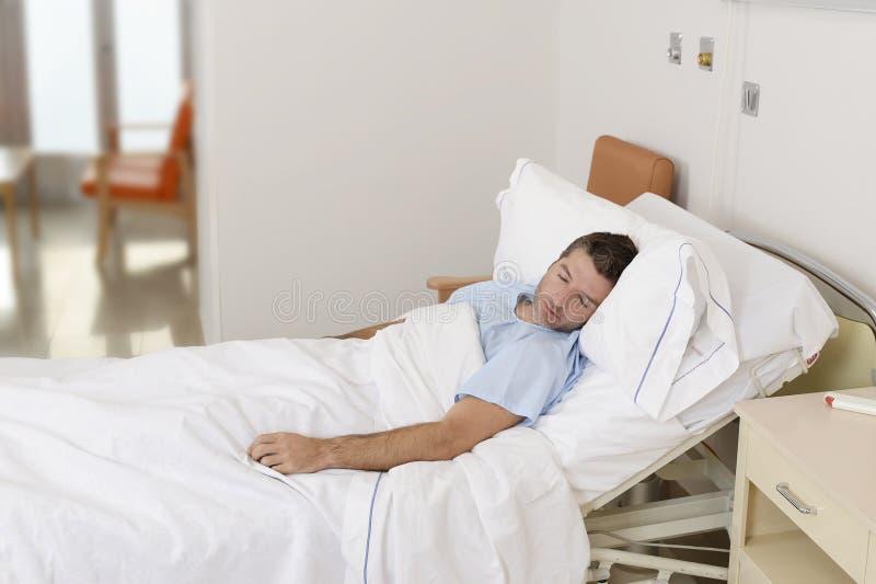 Ung tålmodig man som ligger på sjukhussäng som vilar och sover ha allvarligt medicinskt villkor arkivbilder
