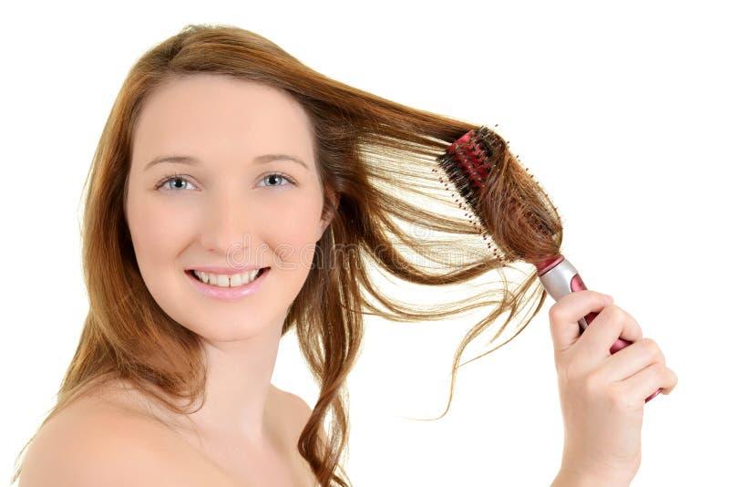 Ung teen flicka som krullar henne hår arkivfoton