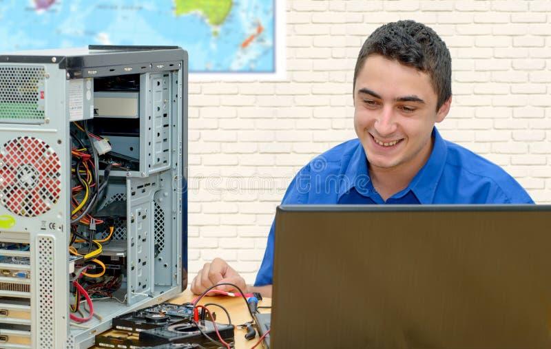 Ung tekniker som arbetar på den brutna datoren i hans kontor royaltyfri fotografi