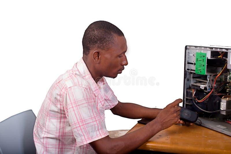 Ung tekniker som reparerar en dator arkivbild