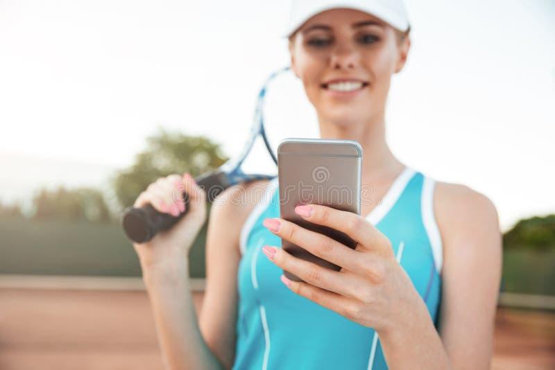 Ung tenniskvinna med telefonen royaltyfri foto