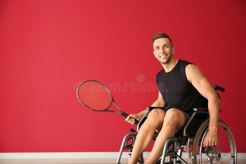 Ung tennisspelare som sitter i rullstol mot färgväggen arkivbilder