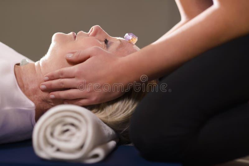 Ung terapeut som ordnar kristaller på den kvinnliga beställaren för reikith royaltyfri bild