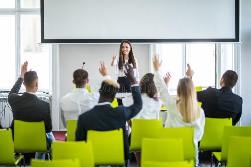 Ung tillfällig asiatisk affärskvinnaledare som gör en presentation och frågar för åsikt i mötet affären chairs konferensskrivbord royaltyfria bilder
