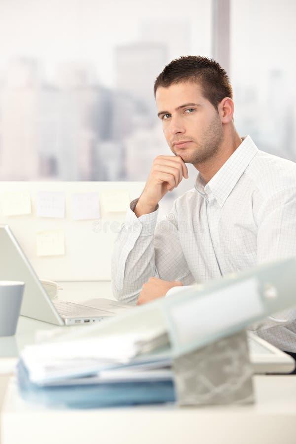 Ung tillfällig kontorsarbetare som sitter på skrivbordet arkivfoton