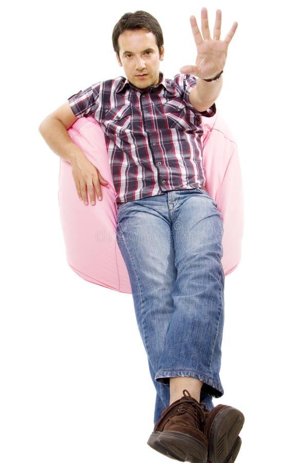 Ung tillfällig man i korrekt läge i en liten rosa sofa arkivbild