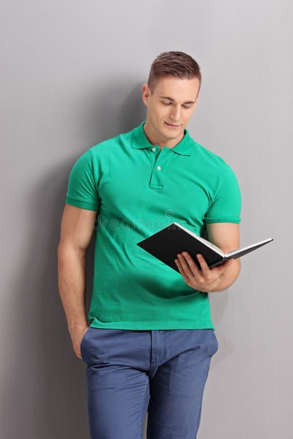 Ung tillfällig man som läser en bok royaltyfri foto