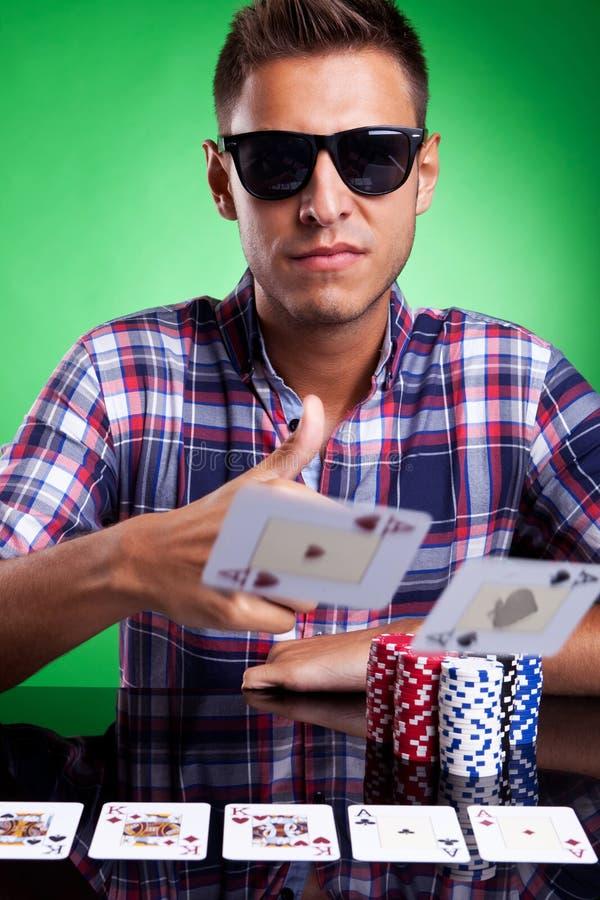 Ung tillfällig pokerspelare som kastar ett par av överdängare royaltyfri foto