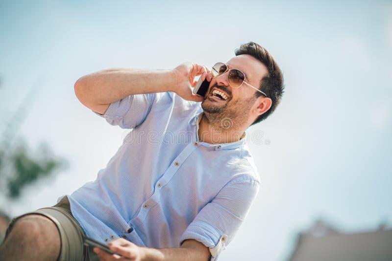 Ung tillf?llig utomhus- maninnehavmobiltelefon och kreditkort royaltyfria foton