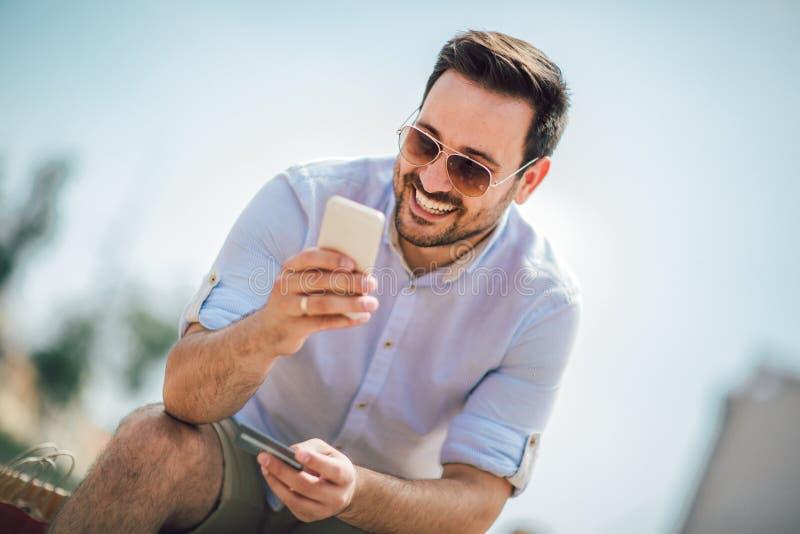 Ung tillf?llig utomhus- maninnehavmobiltelefon och kreditkort royaltyfri fotografi