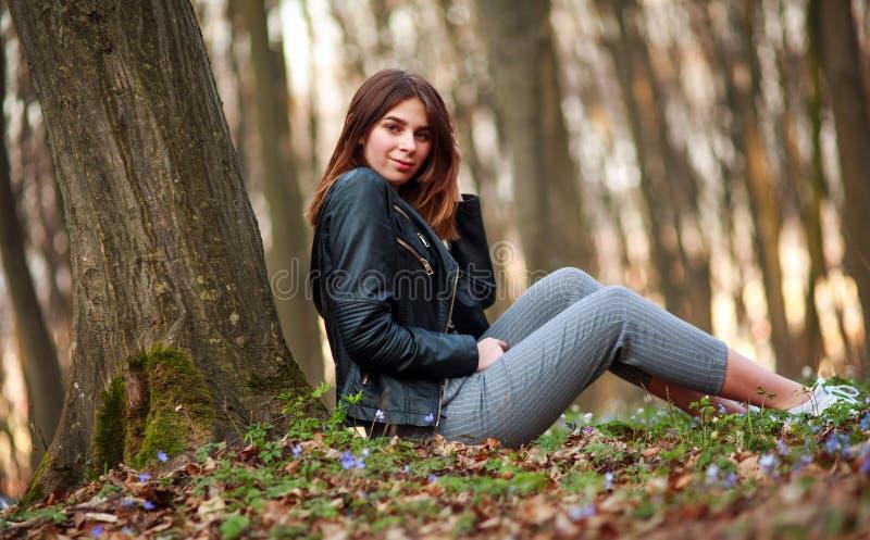 Ung tonårig flicka, i att blomma vårskogen på bakgrund av träd och solnedgången royaltyfri bild