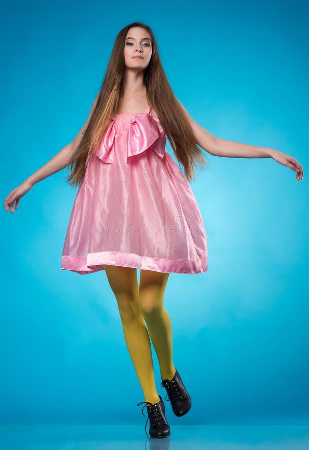 Ung tonårig flicka i en rosa klänningdans royaltyfri foto