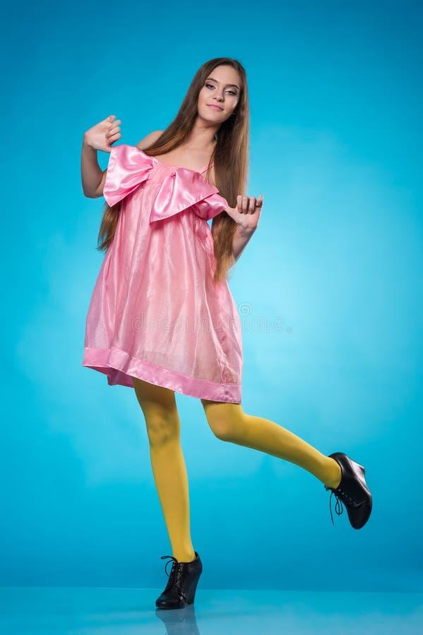 Ung tonårig flicka i en rosa klänningdans royaltyfri fotografi