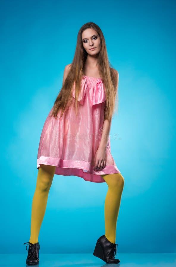 Ung tonårig flicka i rosa posera för klänning arkivbilder