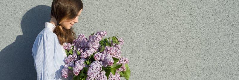 Ung tonårig flicka med buketten av lilan nära utomhus- bakgrund för grå vägg, panorama- baner, flicka i profilen, kopieringsutrym fotografering för bildbyråer