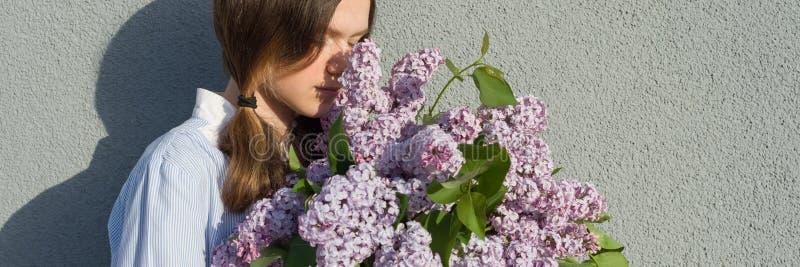 Ung tonårig flicka med buketten av lilan nära utomhus- bakgrund för grå vägg, panorama- baner, flicka i profilen, kopieringsutrym royaltyfri bild