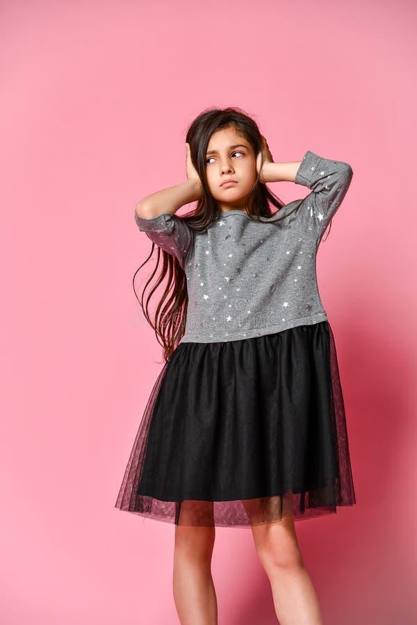Ung tonårig flicka med långt mörkt hår som bär en grå klänning som täcker hennes öron med hennes händer på en rosa bakgrund arkivfoton